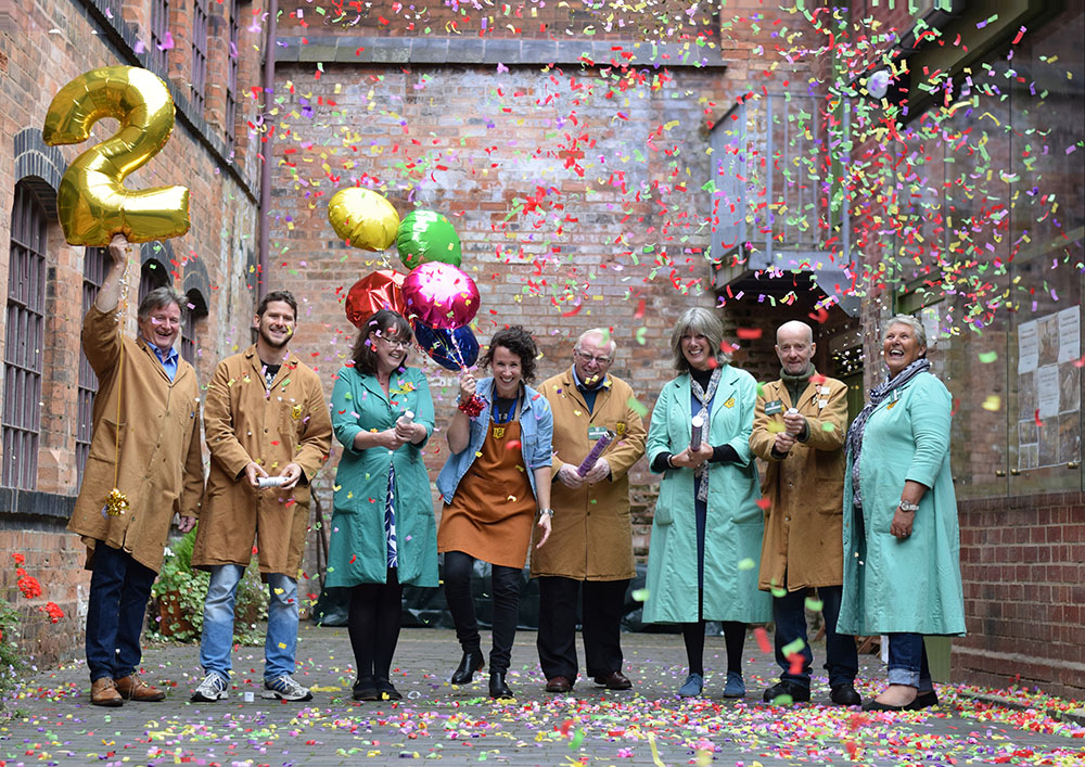 Eight members of the team in Newman Brothers uniforms, some hold balloons, one of which is shaped like the number 2. They fire confetti canons and laugh.