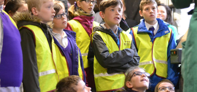 Large group of school children in high vis jackets, listening carefully to tour guide
