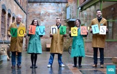 "Volunteers stand in a row, holding up coloured sheets of paper spelling out the word ""volunteers""."