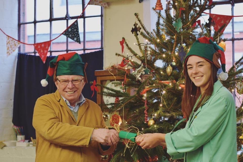 Two smiling volunteers in front of Christmas tree wearing elf hats. They are about to pull a cracker.