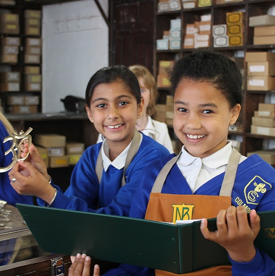 Two smiling girls in blue school uniform holding Newman Brothers catalogue.