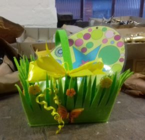 Green Easter basket with a large spotted egg sits on bench surrounded by packages and coffin handles