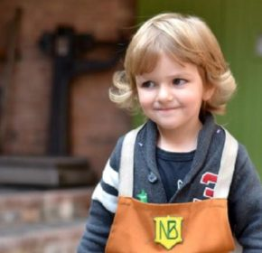 Young boy smiling, he is wearing a brown apron with the Newman Brothers logo on it