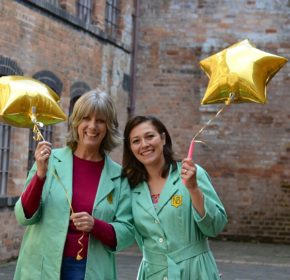 Two happy volunteers in green Newman Brothers coats holding star shaped balloons