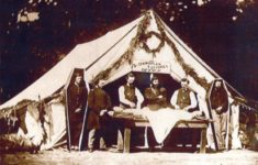 Civil war embalming taking place outside a white tent. There are simple six sided coffins standing on both sides of the tent with soldiers stood inside them.