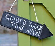Chalkboard sign hanging on door 'Guided tours this way!'