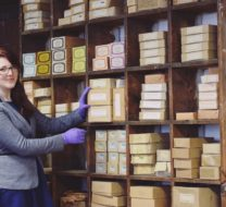 On then left stands a woman with long red hair and grey jacket. Her hand rests on one of the various boxes of coffin handles resting on shelves behind. She wears protective purple gloves.
