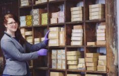 Woman with long red hair and grey jacket stands to the left, her hand rests on box of coffin handles on the shelves behind. She is wearing purple gloves to protect the museum objects.