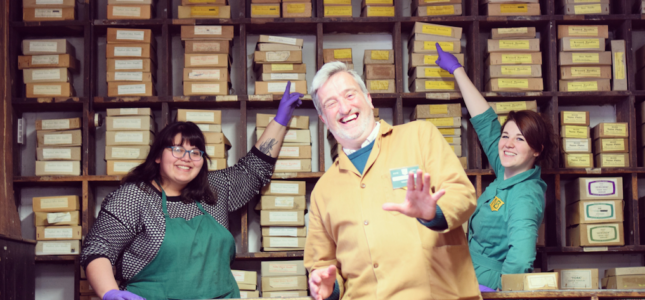 Three happy volunteers. Laughing grey haired man stands in centre, with smiling women either side, pointing to shelves of boxes of coffin handles. All three are wear Newman Brothers in either brown and green.