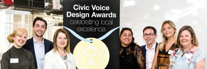 "Civic Voice team smiling, standing either side of a banner for Civic Voice Design Awards, ""Celebrating Local Excellence"""