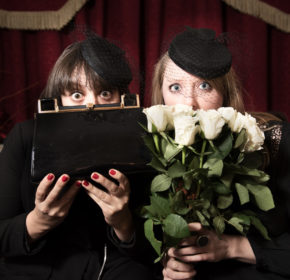Two women in funeral dress, face the camera with wide open eyes, while hiding the bottom halves of their faces with the bouquet of roses and handbag they are holding.