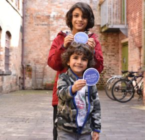 "Two children stand in the courtyard holding small ""The City Beautiful"" blue plaques."