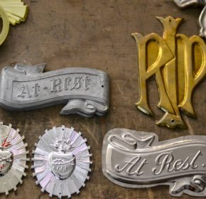 Examples of coffin ornaments. RIP, At rest; are some of the different messages.