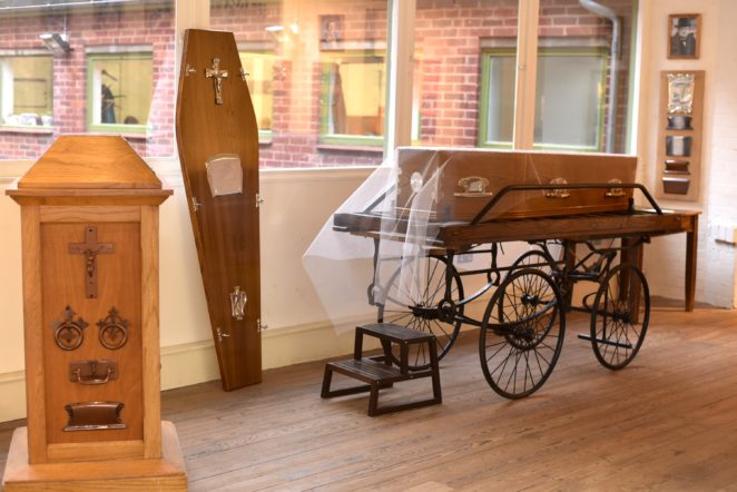 Coffin and coffin furniture on the first floor of the building.