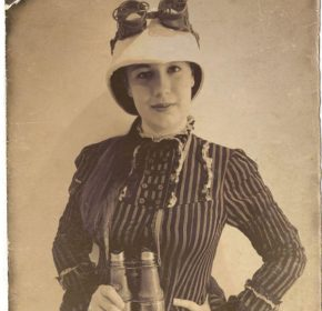 Monster hunter Alice Quatermain in Edwardian clothing, wearing a pith helmet with goggles on top and a pair of binoculars hang around her neck