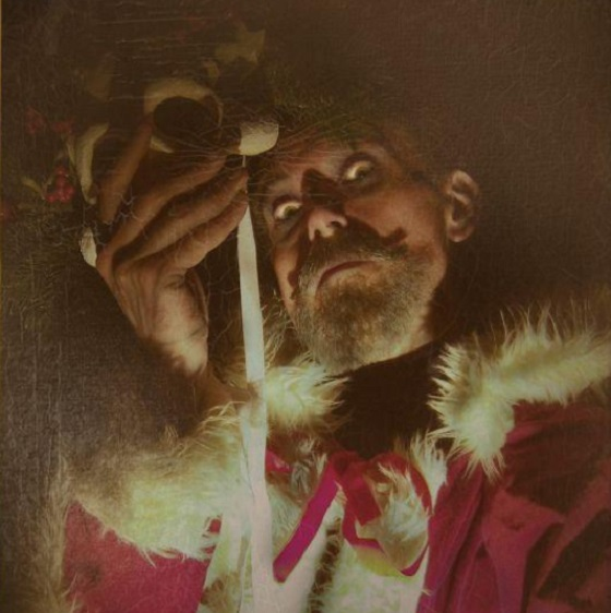 A man with grey moustache and beard wearing Father Christmas clothing looks down at the viewer, he holds a mask in front of his face and is lit from below which gives a spooky feel.