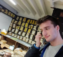 David in the Warehouse holding a coffin handle to his ear as if a telephone receiver
