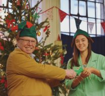 Two volunteers pull a christmas crackers staning in front of a christmas tree