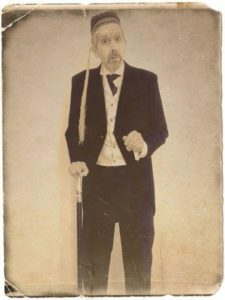 faded aged image of smartly dressed man wearing a smoking cap and leaning on a cane