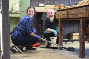 francis and volunteer crouch with vacuum on the stock room floor