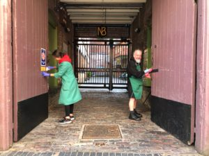 two volunteers clean courtyard doors