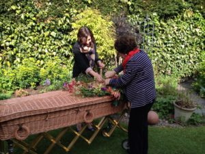 two women in a garden laying flowers on a coffin woven from dried woven plant material