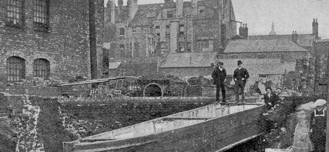 black and white newspaper image. two men stare down at a barge sitting in ruins